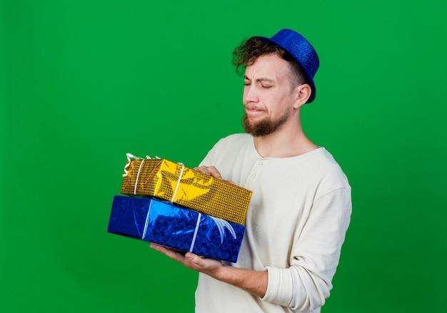 Ragazzo di partito slavo bello giovane dispiaciuto che indossa il cappello del partito che tiene e che esamina i contenitori di regalo che stanno nella vista di profilo isolata su fondo verde con lo spazio della copia