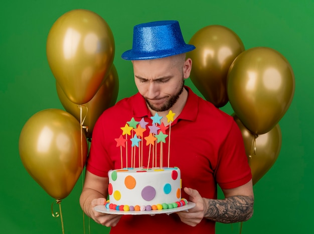 Unpleased young handsome slavic party guy wearing party hat standing in front of balloons holding and looking at birthday cake isolated on green background
