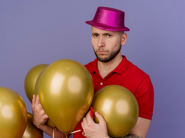 Недовольный молодой красивый славянский тусовщик в партийной шляпе, стоящий возле воздушных шаров, хватая их, глядя в камеру, изолированную на фиолетовом фоне