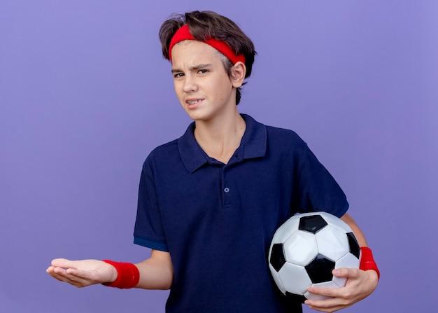 Il giovane ragazzo sportivo bello dispiaciuto che indossa la fascia e i braccialetti con le parentesi graffe dentali che guarda l'obbiettivo che tiene il pallone da calcio che mostra la mano vuota isolata su fondo viola
