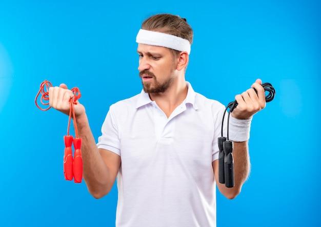 Недовольный молодой красивый спортивный мужчина с повязкой на голову и браслетами, держащими скакалки и смотрящими на них, изолированными на синем пространстве
