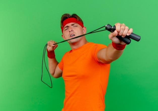 Недовольный молодой красивый спортивный мужчина с повязкой на голову и браслетами, тянущий и вытягивающий скакалку на камеру, изолированную на зеленом фоне с копией пространства