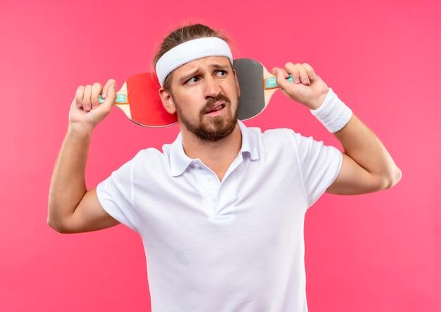 Soddisfatto giovane uomo sportivo bello che indossa la fascia e braccialetti che tengono le racchette da ping pong dietro la sua testa e guardando il lato isolato su spazio rosa