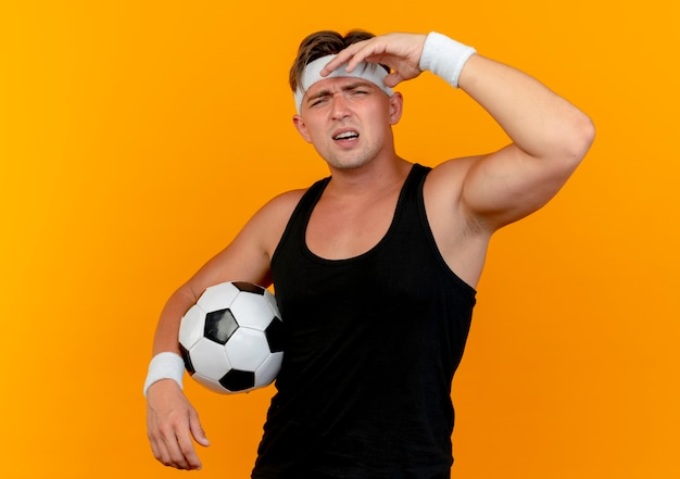 Unpleased young handsome sporty man wearing headband and wristbands holding soccer ball and putting hand near head isolated on orange background