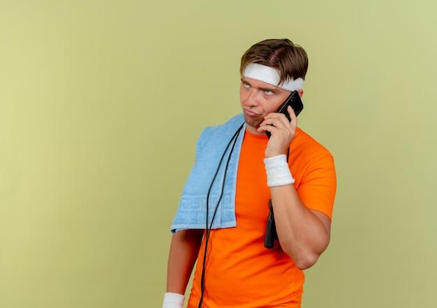 Scontento giovane bello sportivo che indossa fascia e braccialetti con corda per saltare intorno al collo e asciugamano sulla spalla guardando dritto e parlando al telefono