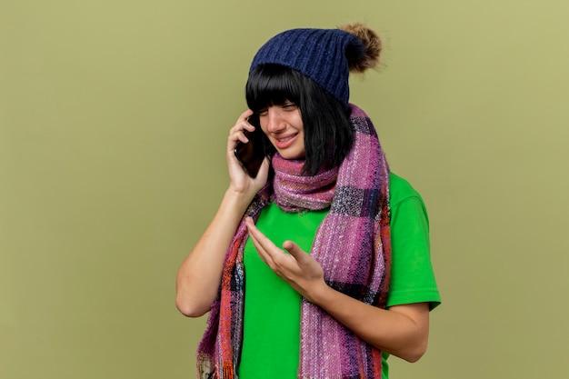 Soddisfatto giovane ragazza caucasica malata indossando cappello invernale e sciarpa parlando al telefono guardando verso il basso che mostra la mano vuota isolata su sfondo verde oliva con spazio di copia