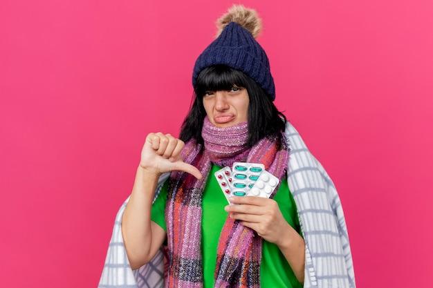 Felice giovane ragazza caucasica malata indossando cappello invernale e sciarpa avvolta in plaid tenendo pillole mediche guardando la telecamera che mostra il pollice verso il basso isolato su sfondo cremisi con spazio di copia