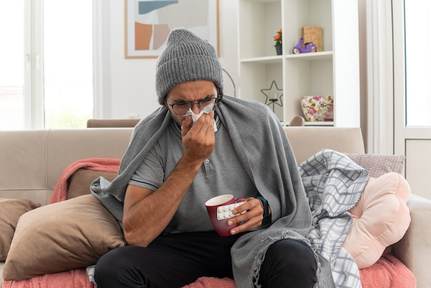 Unpleased young ill caucasian man in optical glasses wearing winter hat wipes his nose with tissue and holds cup with medicine blister pack sitting on couch at living room