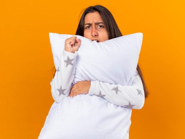 黄色で隔離の枕を抱き締めるカメラを見て不機嫌な若い病気の女の子