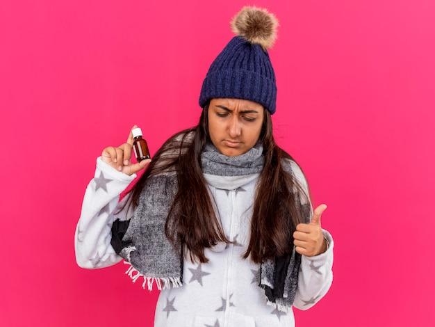 ピンクの背景に分離された親指を示すガラス瓶に薬を保持しているスカーフと冬の帽子をかぶって見下ろしている不機嫌な若い病気の女の子