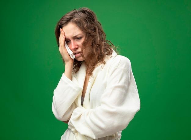 Giovane ragazza malata dispiaciuta che guarda la veste bianca da portare laterale che mette la mano sulla faccia isolata sul verde