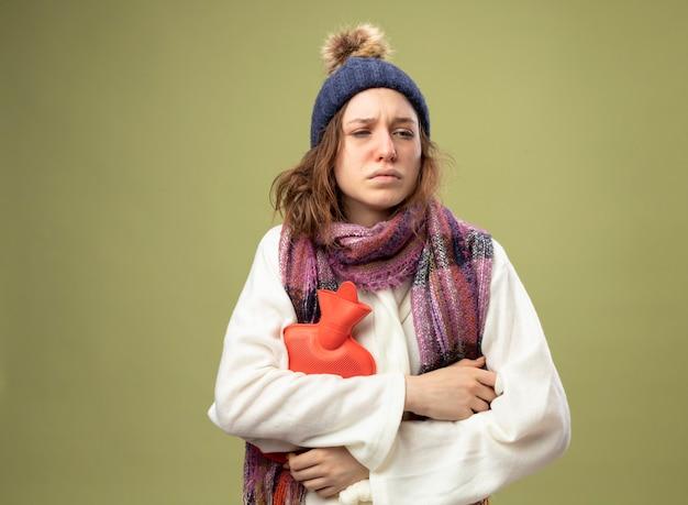 Giovane ragazza malata dispiaciuta che guarda al lato che indossa la veste bianca e il cappello invernale con la sciarpa che tiene la borsa dell'acqua calda isolata su verde oliva