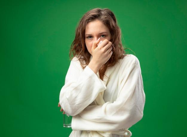 Giovane ragazza malata dispiaciuta guardando dritto davanti a sé che indossa una veste bianca mettendo la mano sulla bocca isolata sul verde