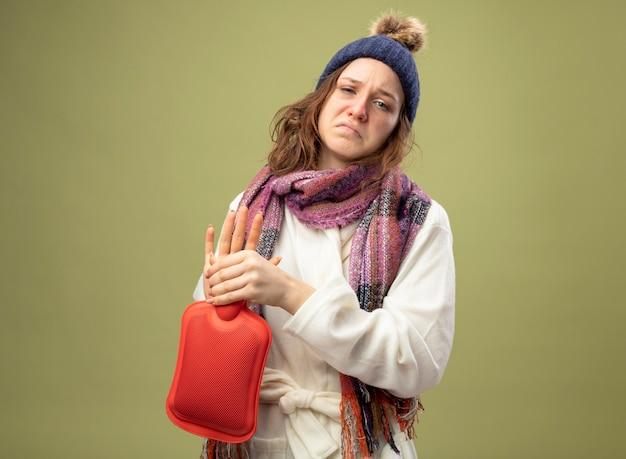 Giovane ragazza malata dispiaciuta che guarda dritto davanti a sé indossa una veste bianca e un cappello invernale con la sciarpa che tiene la borsa dell'acqua calda isolata su verde oliva