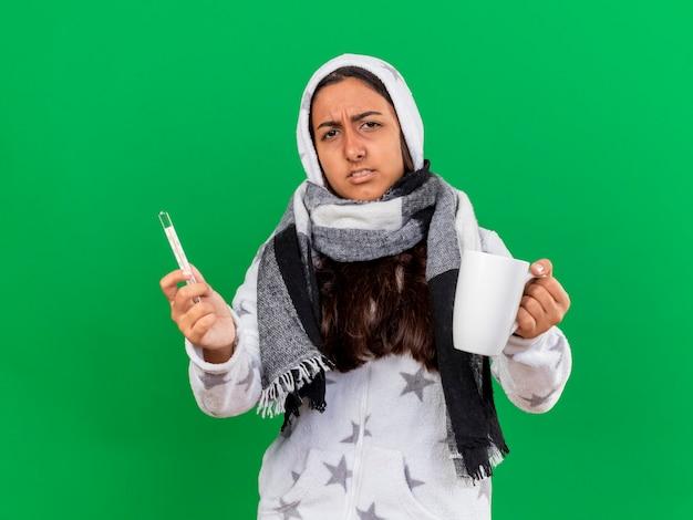 Giovane ragazza malata dispiaciuta che mette sulla sciarpa wearin cappuccio che tiene fuori il termometro con la tazza di tè alla macchina fotografica isolata su fondo verde
