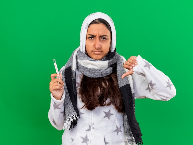 Giovane ragazza malata dispiaciuta che indossa il termometro della holding della sciarpa wearin del cappuccio che mostra il pollice giù isolato sul verde