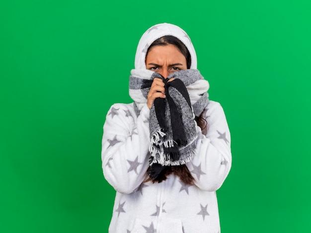 緑の背景に分離されたスカーフでスカーフで覆われた顔にフードを身に着けている不機嫌な若い病気の女の子