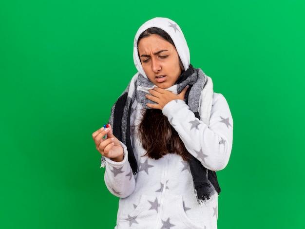 不愉快な若い病気の少女は、コピースペースで緑の背景に分離された丸薬を保持し、見てフードウェアインスカーフを身に着けています