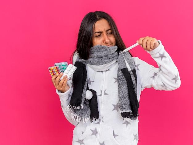 Giovane ragazza malata che indossa e ha coperto la bocca con la sciarpa che tiene le pillole e guardando il termometro in mano isolato su sfondo rosa