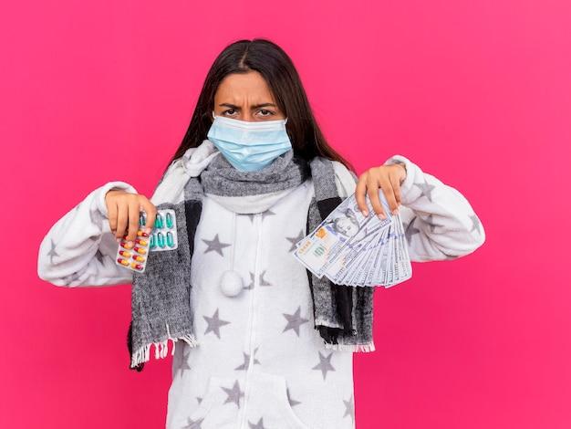Giovane ragazza malata dispiaciuta che indossa la mascherina medica con la sciarpa che tiene le pillole con contanti isolati sul colore rosa