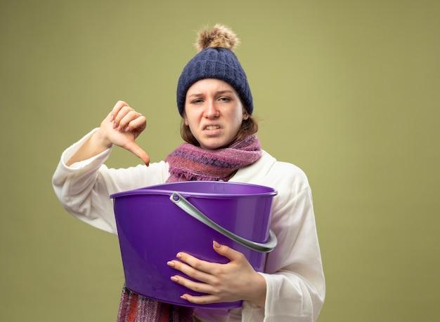 올리브 그린에 고립 된 엄지 손가락을 보여주는 플라스틱 양동이 들고 스카프와 흰 가운과 겨울 모자를 쓰고 불쾌한 어린 아픈 소녀