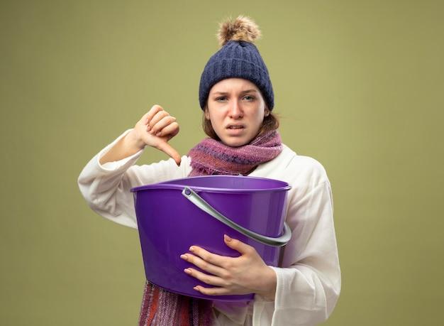 白いローブと冬の帽子を身に着けている不機嫌な若い病気の女の子は、オリーブグリーンで隔離された親指を下に示すプラスチック製のバケツを保持しているスカーフと
