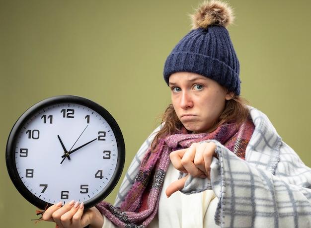Недовольная молодая больная девушка в белом халате и зимней шапке с шарфом держит настенные часы, завернутые в плед, показывая большой палец вниз, изолированный на оливково-зеленом