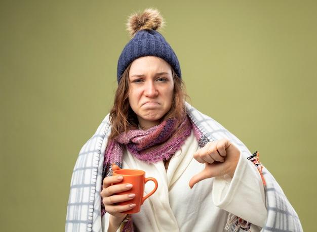 白いローブと冬の帽子を身に着けている不機嫌な若い病気の女の子は、オリーブグリーンで隔離された親指を下に示す格子縞のお茶のカップを保持している格子縞に包まれたスカーフ