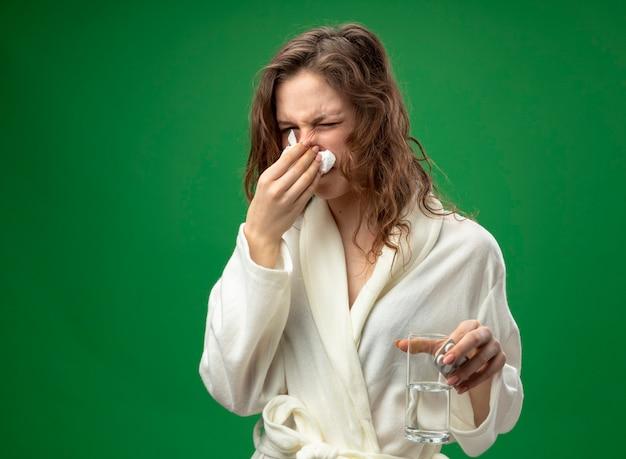 Giovane ragazza malata dispiaciuta che indossa una veste bianca che tiene il bicchiere d'acqua pulendosi il naso con un tovagliolo isolato su verde