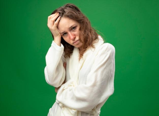 Недовольная молодая больная девушка в белом халате, положив руку на голову