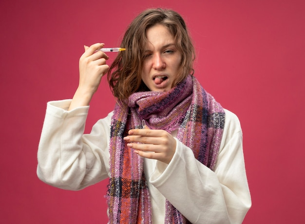 Giovane ragazza malata dispiaciuta che indossa veste bianca e sciarpa che tiene la fiala e che fa iniezione al tempio con la siringa isolata sulla parete rosa