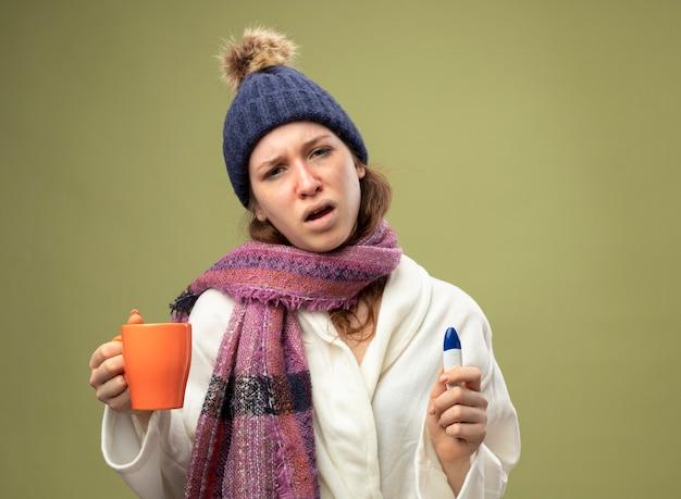 Giovane ragazza malata dispiaciuta che indossa una veste bianca e cappello invernale con sciarpa che tiene tazza di tè con termometro isolato su verde oliva con spazio di copia