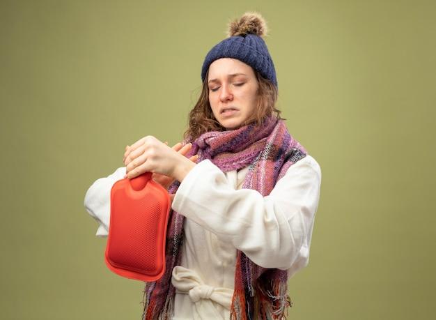 Giovane ragazza malata dispiaciuta che indossa una veste bianca e cappello invernale con sciarpa che tiene e guardando la borsa dell'acqua calda isolata su verde oliva