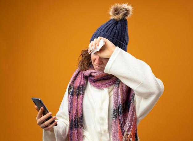 Giovane ragazza malata dispiaciuta che indossa una veste bianca e cappello invernale con sciarpa che tiene e guardando il telefono mettendo la mano sulla fronte isolata sulla parete arancione