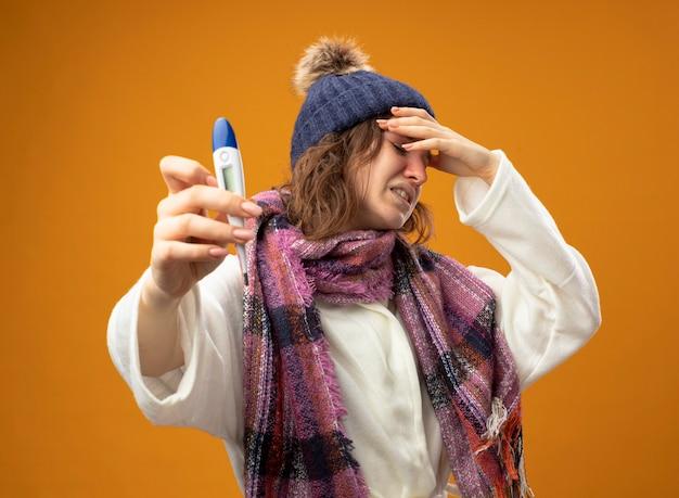 Giovane ragazza malata dispiaciuta che indossa una veste bianca e cappello invernale con sciarpa che tiene fuori il termometro che mette la mano sulla fronte isolata sulla parete arancione