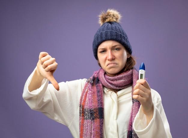 Giovane ragazza malata dispiaciuta che indossa una veste bianca e cappello invernale con sciarpa che tiene il termometro che mostra il pollice verso il basso isolato sulla porpora