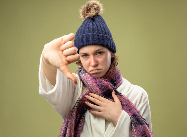 Giovane ragazza malata dispiaciuta che indossa veste bianca e cappello invernale con sciarpa che mostra il pollice verso il basso isolato su verde oliva