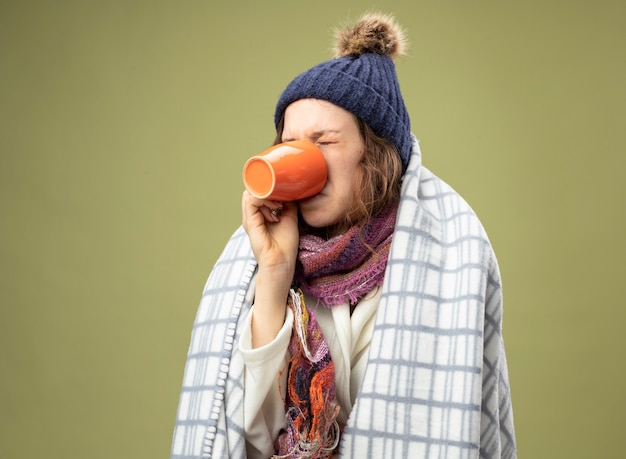 Unpleased young ill girl wearing white robe and winter hat with scarf wrapped in plaid drinks tea isolated on olive green