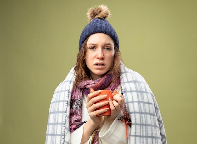 Giovane ragazza malata dispiaciuta che indossa una veste bianca e cappello invernale con sciarpa avvolta in un plaid che tiene tazza di tè isolato su verde oliva