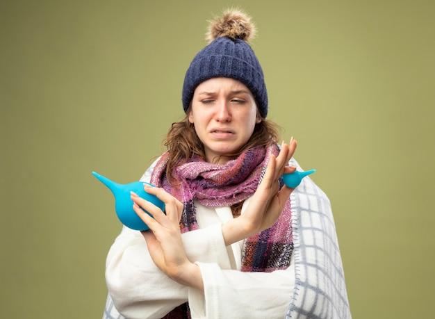 Giovane ragazza malata che indossa una veste bianca e cappello invernale con sciarpa avvolta in un plaid che tiene clisteri e mani incrociate isolate su verde oliva