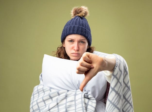 Giovane ragazza malata dispiaciuta che indossa una veste bianca e cappello invernale con sciarpa avvolta in un plaid abbracciato cuscino che mostra il pollice verso il basso