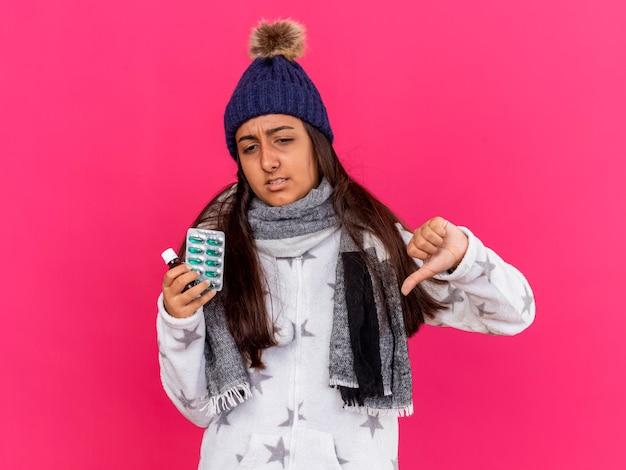 ピンクの背景で隔離の親指を示すガラス瓶に薬を保持しているスカーフと冬の帽子をかぶって不機嫌な若い病気の女の子