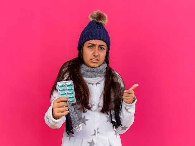 ピンクで隔離されたジェスチャーを示すピルを保持しているスカーフと冬の帽子をかぶっている不機嫌な若い病気の女の子