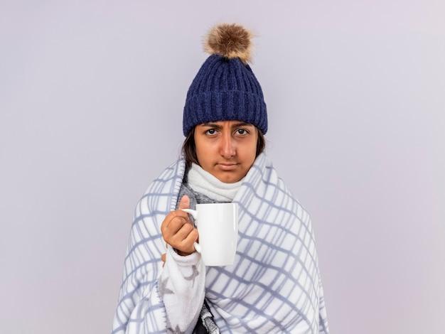 白で隔離のお茶のカップを保持している格子縞に包まれたスカーフと冬の帽子をかぶっている不機嫌な若い病気の女の子