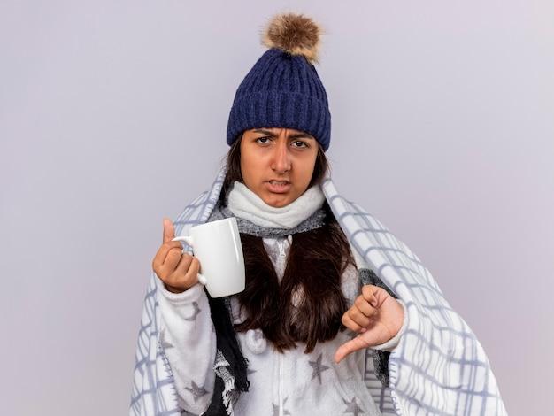 親指を下に見せてお茶のカップを保持している格子縞に包まれたスカーフと冬の帽子をかぶっている不機嫌な若い病気の女の子