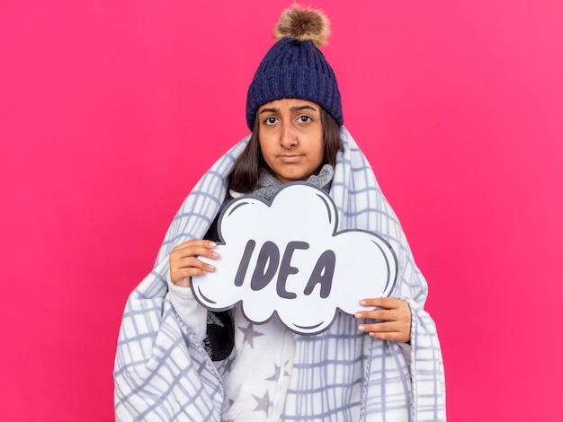 Giovane ragazza malata dispiaciuta che indossa il cappello invernale con sciarpa avvolta in plaid tenendo idea bolla isolata su sfondo rosa