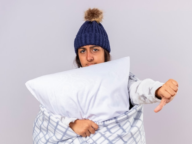 Unpleased young ill girl wearing winter hat with scarf wrapped in plaid hugging pillow showing thumb down