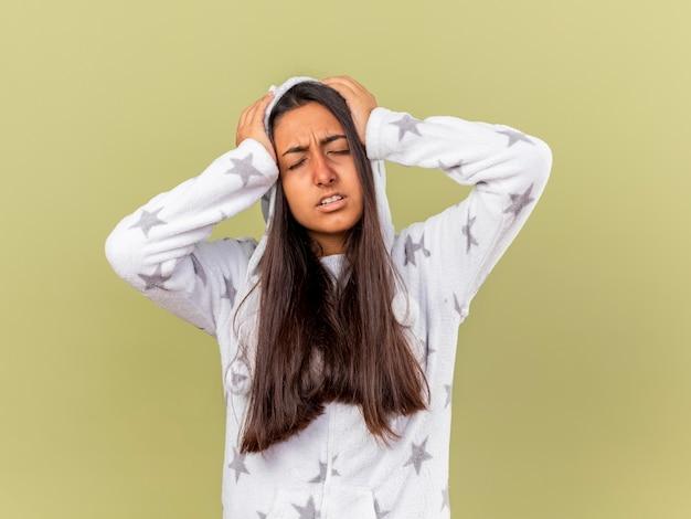 La giovane ragazza malata spiacevole con gli occhi chiusi che mette sul cappuccio ha afferrato la testa dolorante isolata su fondo verde oliva
