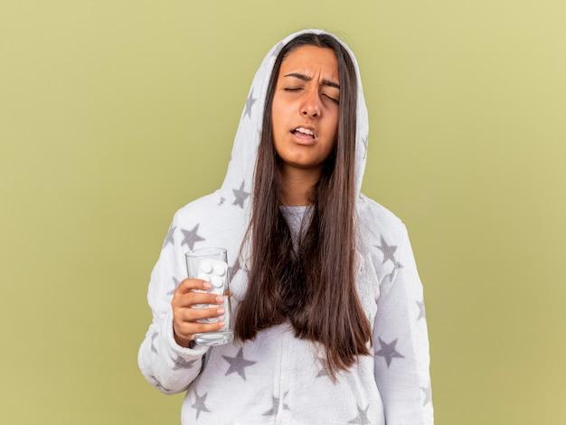 Giovane ragazza malata dispiaciuta con gli occhi chiusi che mette sul cappuccio che tiene acqua di vetro con le pillole isolate su fondo verde oliva