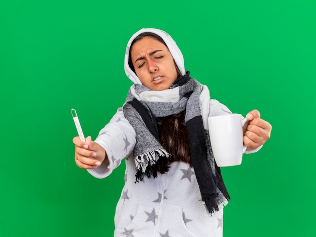 Unpleased young ill girl with closed eyes putting on hood wearin scarf holding out thermometer with cup of tea isolated on green background